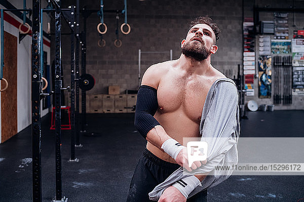 Exhausted young man taking break in gym