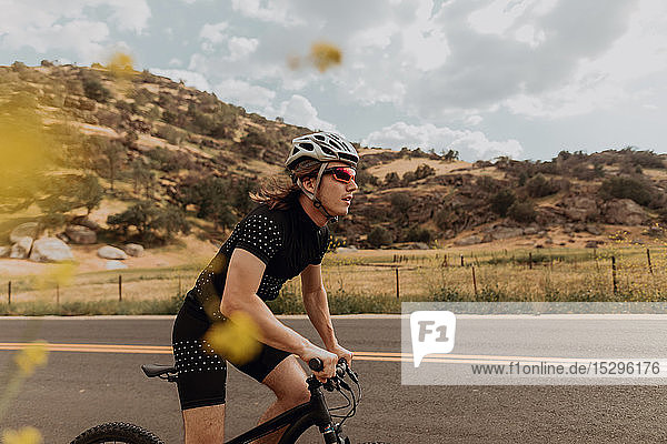 Young male cyclist cycling on rural road  side view  Exeter  California  USA