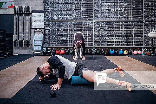 Junger Mann massiert Oberschenkel mit Schaumstoffrolle im Fitnessstudio