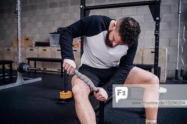 Junger Mann massiert Oberschenkel mit Muskelrollstab im Fitnessstudio