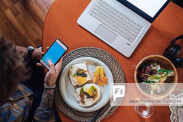 Mittelgroßer erwachsener Mann  der am Tisch ein Spiegelei essen will  Blick auf Smartphone  Draufsicht