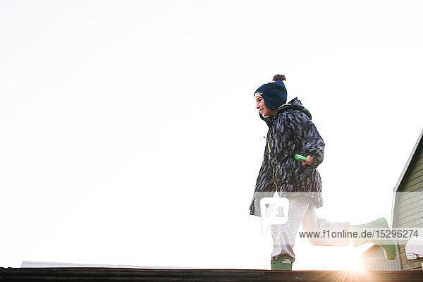 Junge mit Strickmütze  der über die sonnenbeschienene Skateboard-Rampe läuft  Blickwinkel niedrig