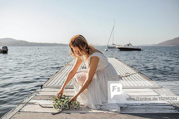 Junge Braut im Brautkleid legt Brautstrauss am Seepier nieder  Stresa  Piemont  Italien