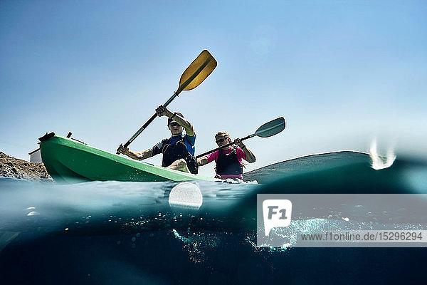 Teenager Junge und Mutter beim Kajakfahren auf dem Meer  Blick auf die Oberfläche  Limnos  Khios  Griechenland Teenager Junge und Mutter beim Kajakfahren auf dem Meer, Blick auf die Oberfläche, Limnos, Khios, Griechenland