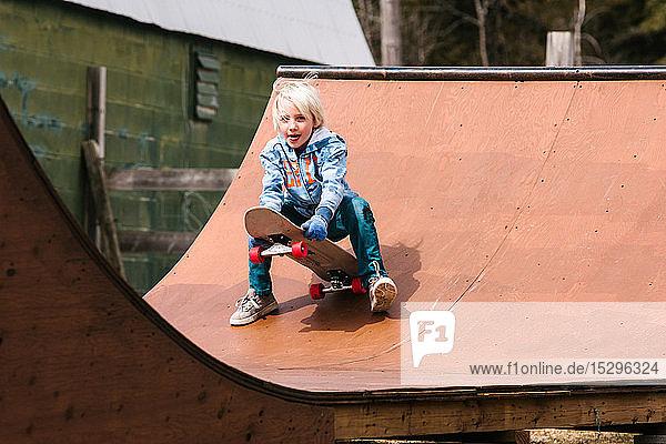 Junge bereitet sich darauf vor  sich auf einer hölzernen Skateboard-Rampe auf ein Skateboard zu setzen
