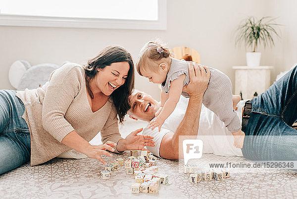 Mutter und Vater liegen auf dem Kinderzimmerboden und spielen mit der kleinen Tochter