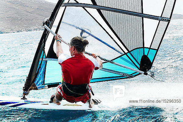 Junger Mann beim Windsurfen auf der Meereswelle  Rückansicht  Limnos  Khios  Griechenland Junger Mann beim Windsurfen auf der Meereswelle, Rückansicht, Limnos, Khios, Griechenland