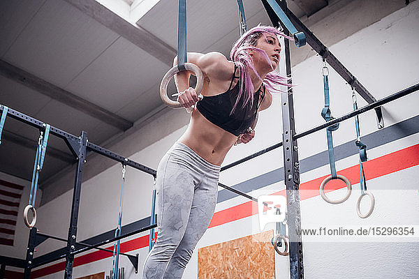 Young woman balancing on gymnastic rings in gym
