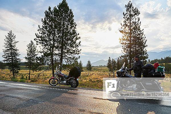 Senior male motorcyclist on rural roadside with motorbike  Dawson Creek  Canada