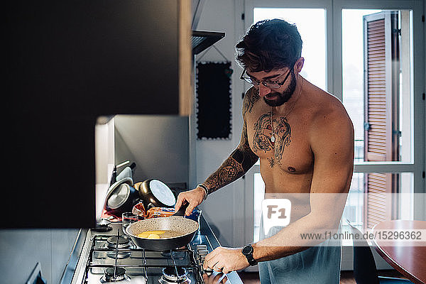 Mid adult man with tattooed chest using gas hob