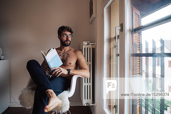 Mid adult man with tattooed chest sitting on chair looking out through window