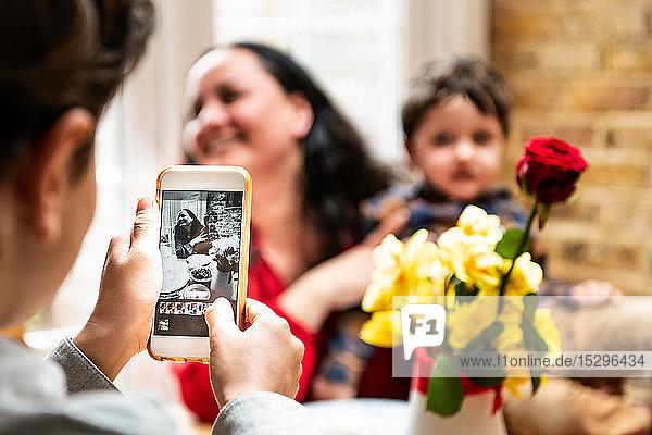 Junge macht Smartphone-Foto Mutter und Kleinkind Bruder feiern Muttertag  Blick über die Schulter