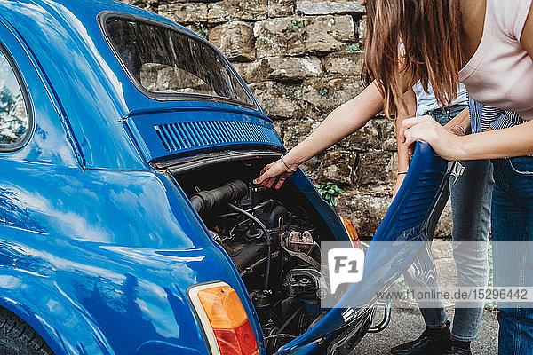 Freunde reparieren abgewürgtes Auto auf dem Land