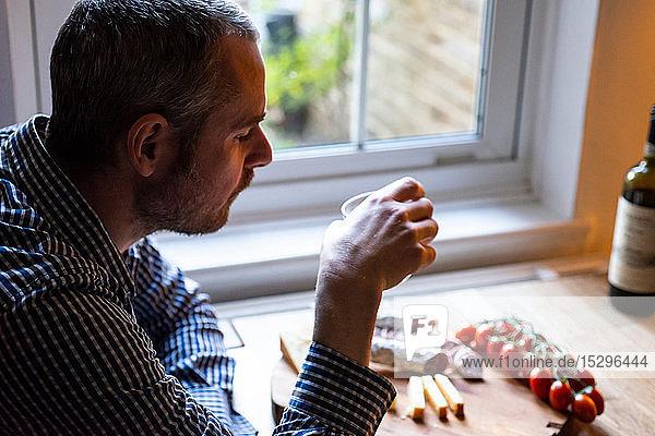Mann trinkt Wein und isst mediterranes Essen im Café