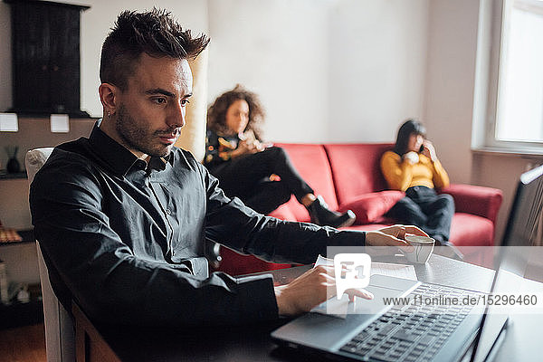 Man using laptop  friends relaxing in background in home office