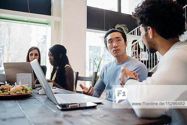 Junge Geschäftsleute diskutieren an Café-Tisch