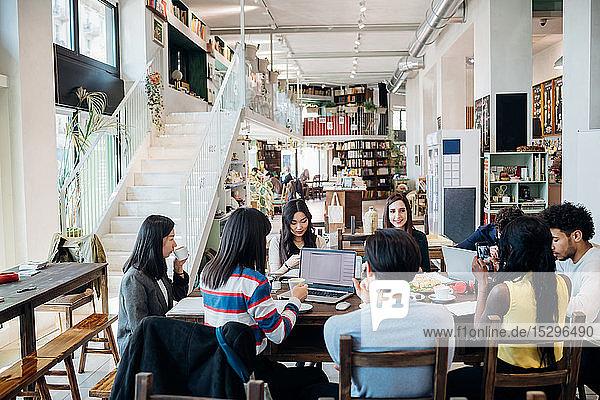 Männliche und weibliche Geschäftsteambesprechung beim Arbeitsessen am Cafétisch