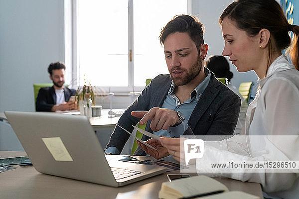 Junge männliche und weibliche Kreative aus der Wirtschaft treffen sich in einem Großraumbüro