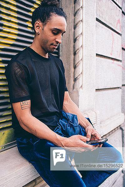 Junger Mann benutzt Smartphone am Fensterbrett eines Gebäudes