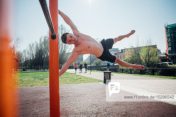 Calisthenics at outdoor gym  bare chested young man swinging horizontally on exercise equipment