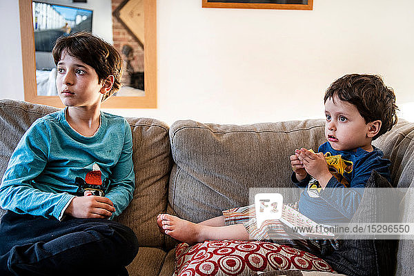 Brüder schauen ungläubig auf dem Sofa auf