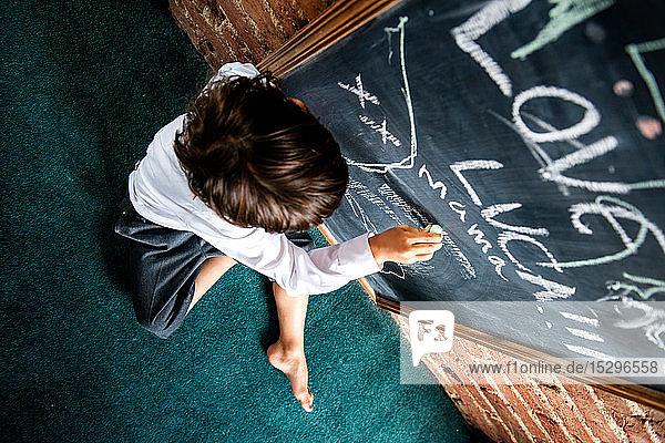 Junge in Schuluniform schreibt zu Hause an Tafel