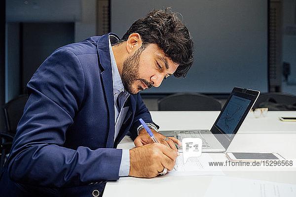 Geschäftsmann schreibt Notizen und benutzt Laptop im Büro