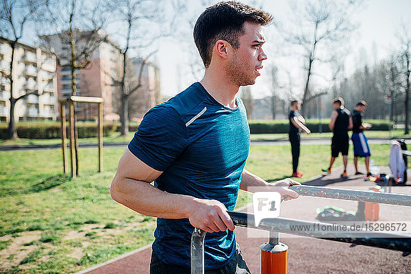 Calisthenics at outdoor gym  young man preparing to use parallel bars