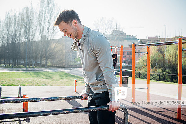 Calisthenics at outdoor gym  young man on parallel bars
