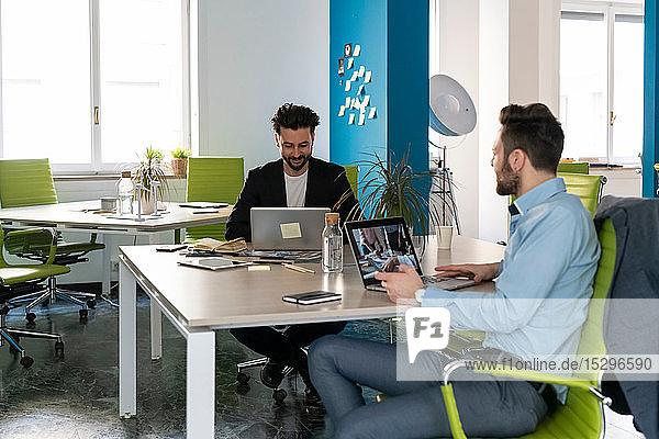 Zwei männliche Geschäftskreative benutzen Laptops am Büroschreibtisch