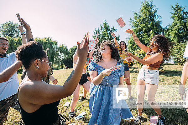 Group of friends dancing  throwing playing cards into air in park