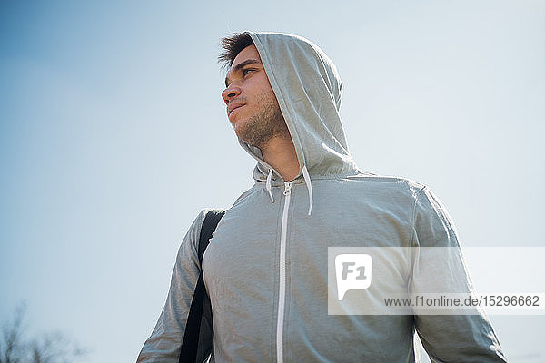 Calisthenics in park  young man in hoody against blue sky