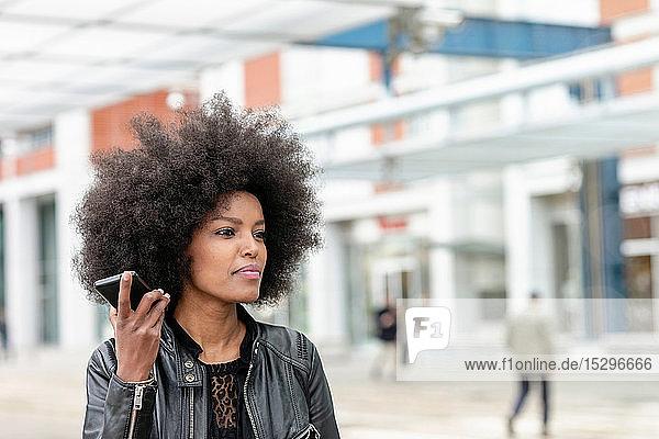 Junge Frau mit Afro-Haaren am Stadtbahnhof  die ein Smartphone hört