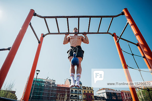 Calisthenics at outdoor gym  young man doing pull ups on exercise equipment with kettlebell on waist harness