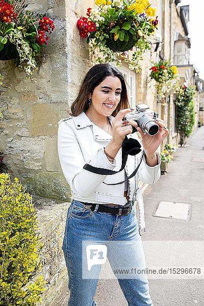 Junge Frau auf der Dorfstraße beim Betrachten von Fotos mit einer Digitalkamera  Cotswolds  England