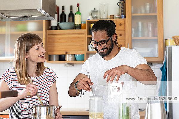 Multi-ethnisches Paar redet und kocht in der Küche