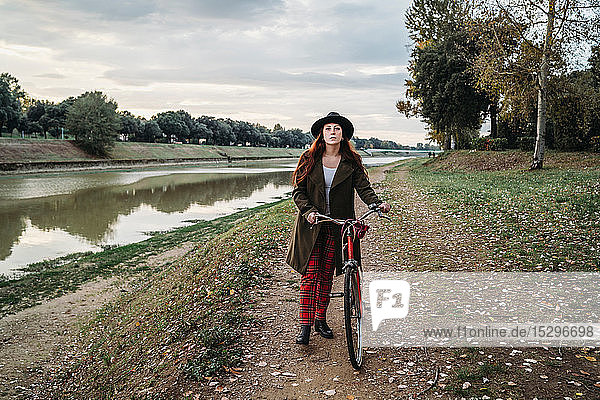 Young woman with long red hair pushing bicycle on riverside  full length portrait  Florence  Tuscany  Italy