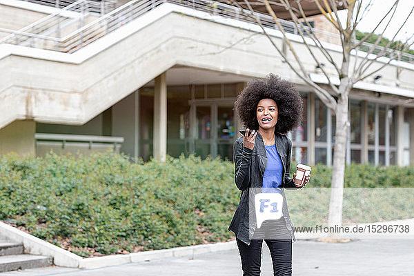 Junge Frau mit Afro-Haaren in der Stadt  geht zu Fuß und spricht mit Smartphone