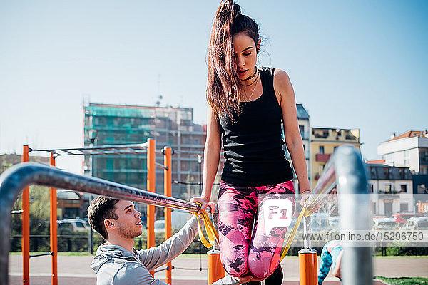 Calisthenics-Kurs im Freien  männlicher Trainer ermutigt junge Frau am Barren