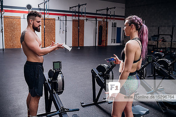 Young woman and man training together  preparing to use rowing machines in gym