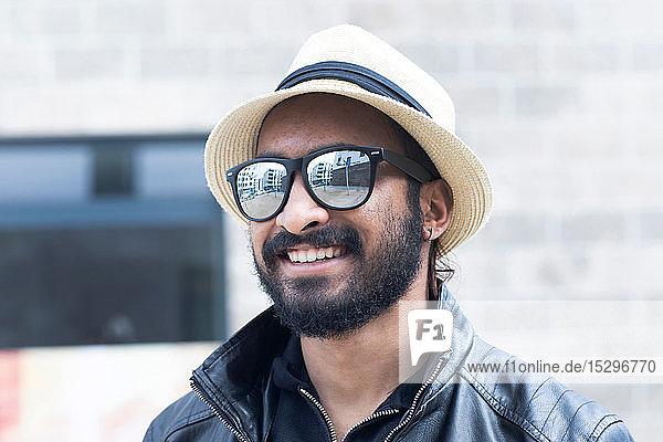 Porträt eines lächelnden Mannes mit Hut und Sonnenbrille