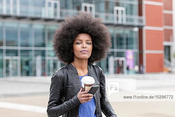 Junge Frau mit Afrofrisur in der Stadt  mit Smartphone und Kaffee zum Mitnehmen  Porträt