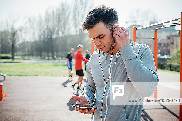 Calisthenics class at outdoor gym  young man putting in earphones