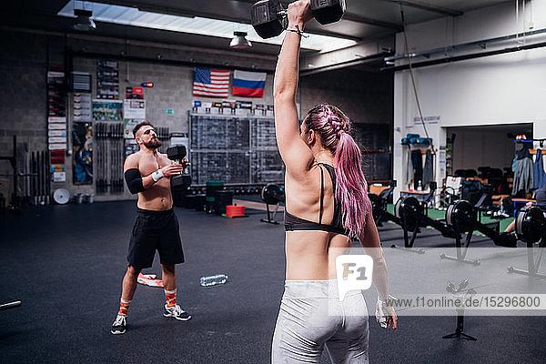 Training junger Frauen und Männer  Hanteln im Fitnessstudio heben