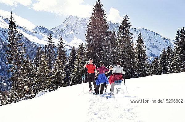 Reifes Paar und Töchter machen eine Pause beim Schneeschuhwandern in schneebedeckter Berglandschaft  Steiermark  Tirol  Österreich