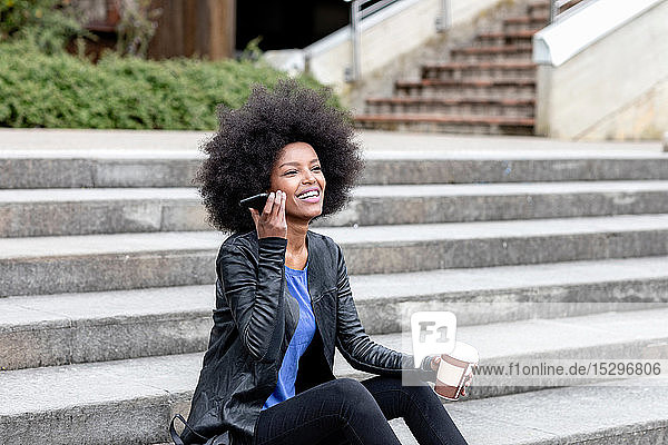Glückliche junge Frau mit Afro-Haaren sitzt auf einer Stadttreppe und hört ein Smartphone