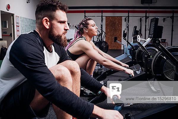 Junge Frau und Mann trainieren gemeinsam an Rudergeräten in der Turnhalle  Seitenansicht