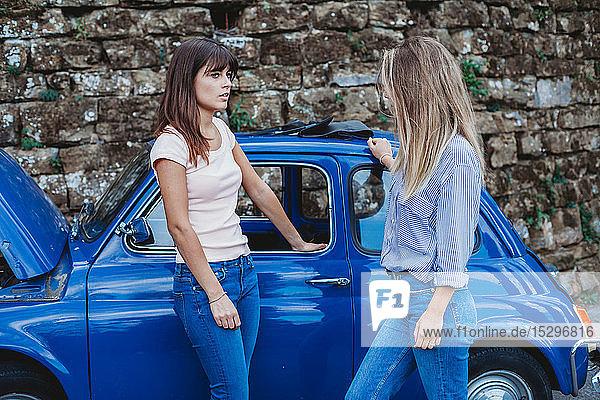 Freunde unterhalten sich neben abgewürgtem Auto auf dem Land
