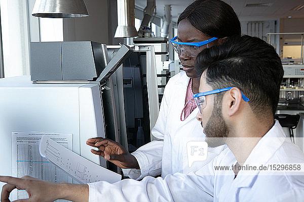 Junge Wissenschaftlerinnen und Wissenschaftler diskutieren im Labor über Papierarbeit