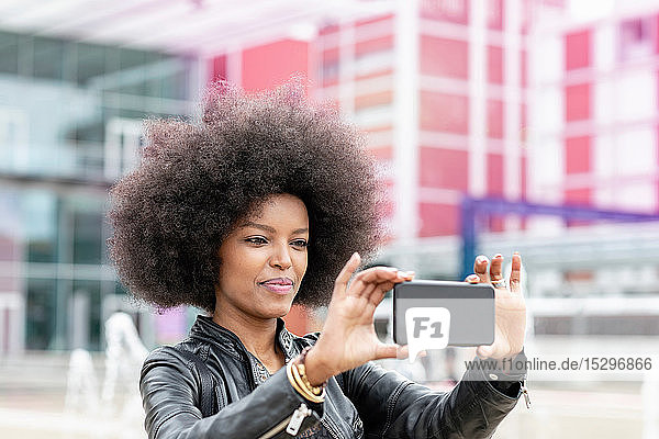 Junge Frau mit Afro-Haaren am Stadtbahnhof  nimmt Smartphone-Selfie